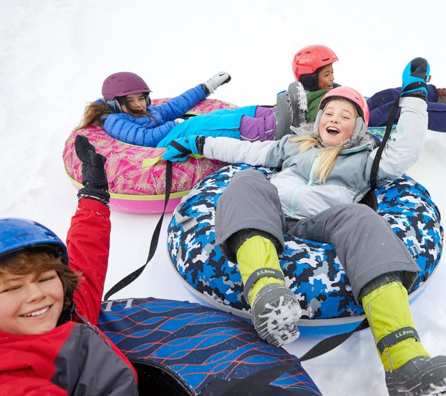 4 kids sledding on soci snow tubes