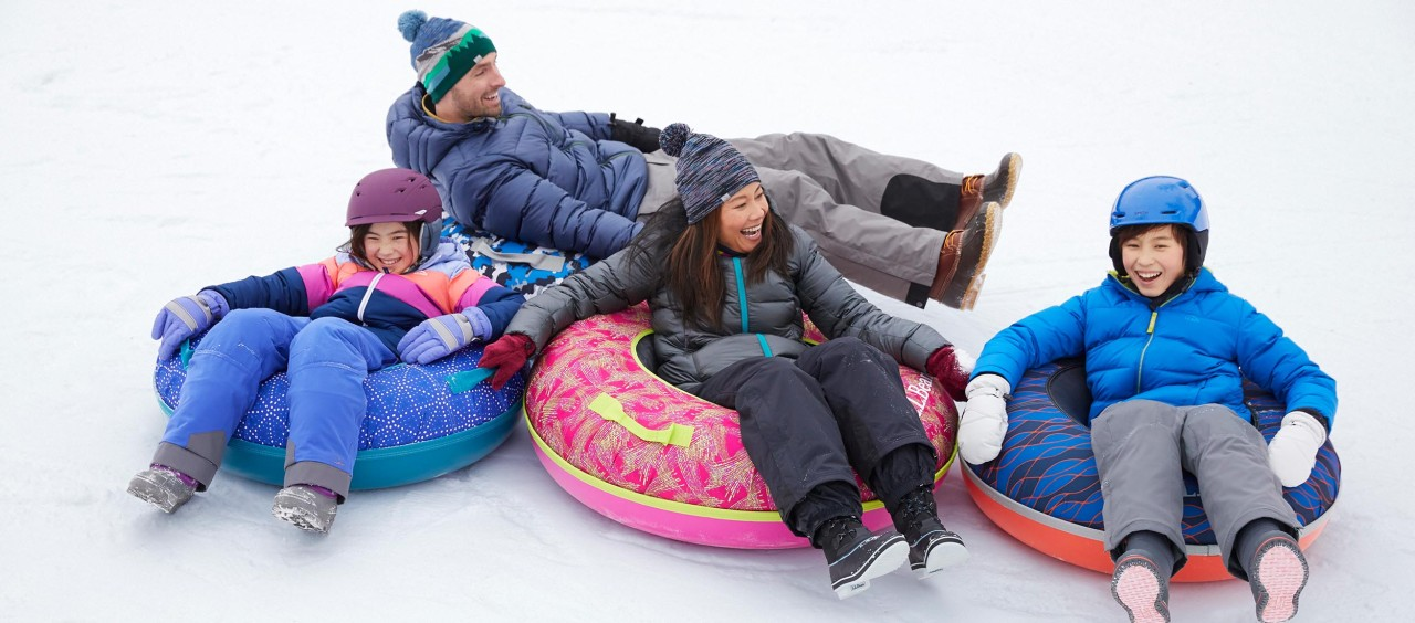Smiling family of 4 on Sonic Snow Tubes.