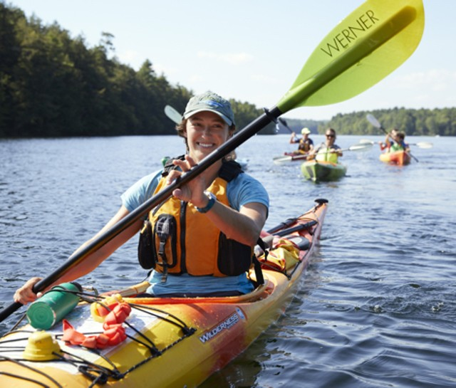 A smiling woman paddling a kayak with 3 others in kayaks behind her.