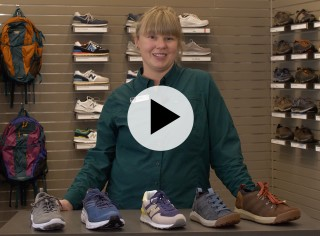An L. L. Bean Customer Service Rep standing behind a table of walking shoes with a play video symbol.