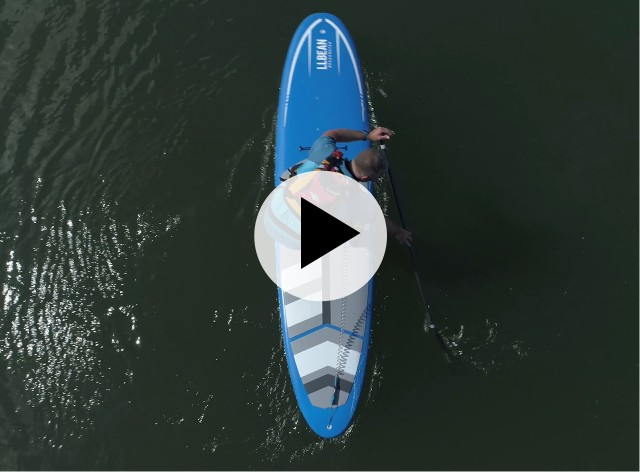 An overhead view of a man paddling on SUP, a play video icon in the center.