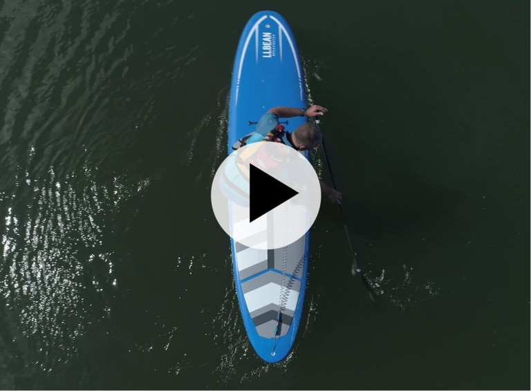 An overhead shot of a man paddling a SUP, a play video symbol in center.