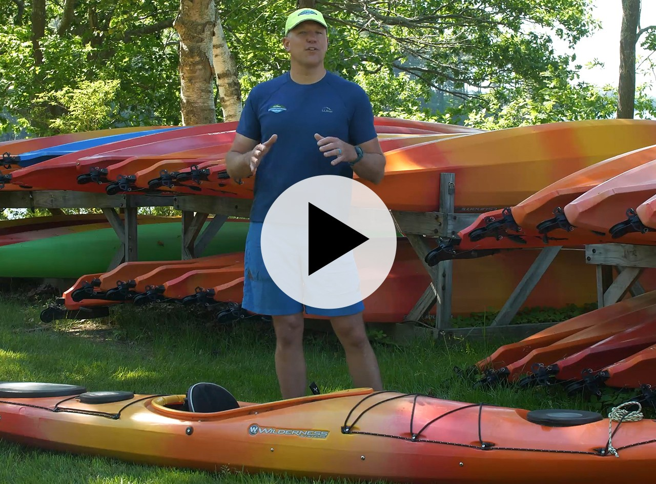 A kayak instructor outside with several kayaks, play video symbol in the center.
