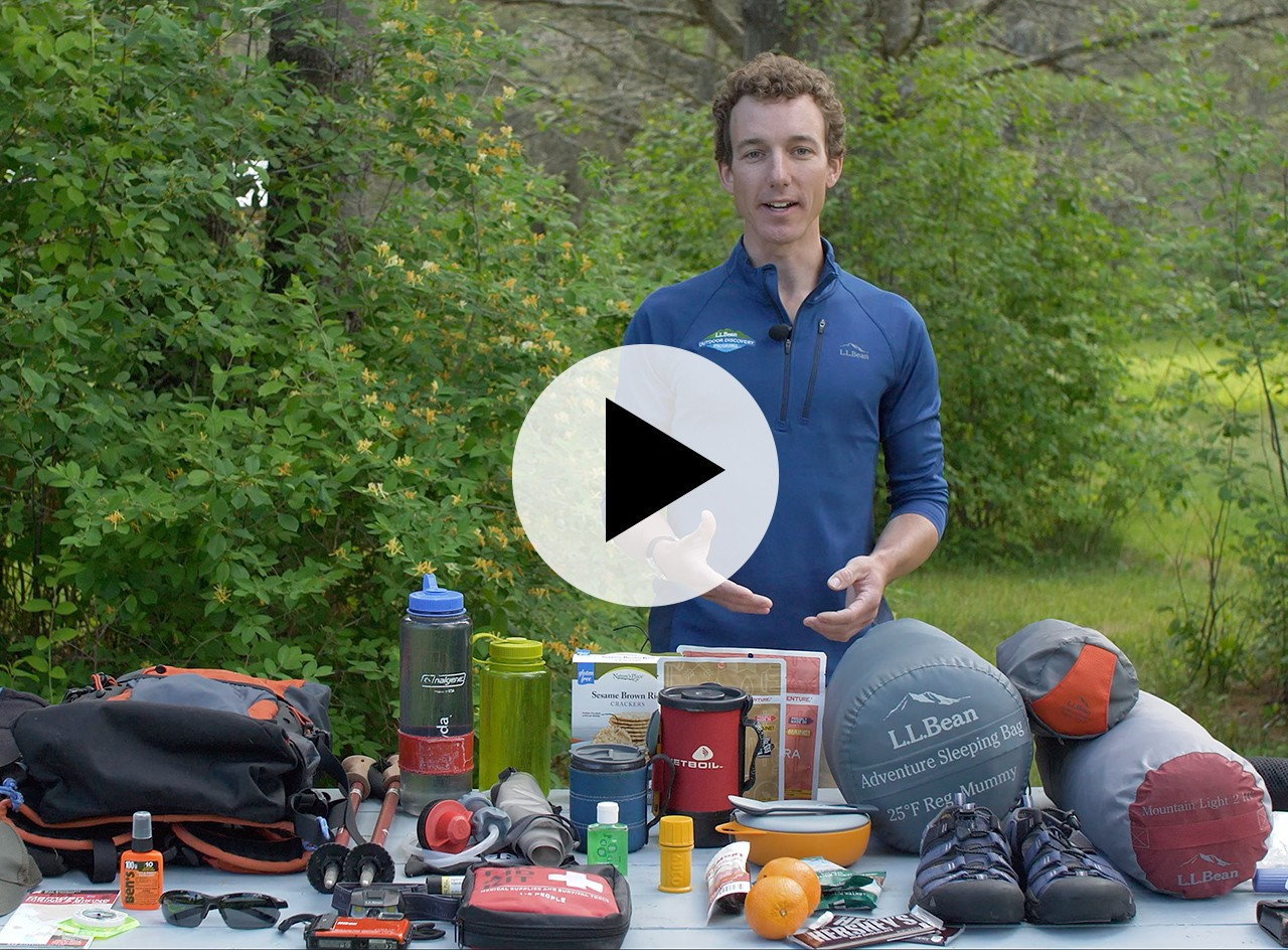 An L.L.Bean instructor behind a table covered with things to consider bringing on a hike, a play video icon in the center.