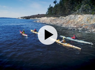 4 kayakers paddling on the ocean near the rocky shore, a play video icon in the center.