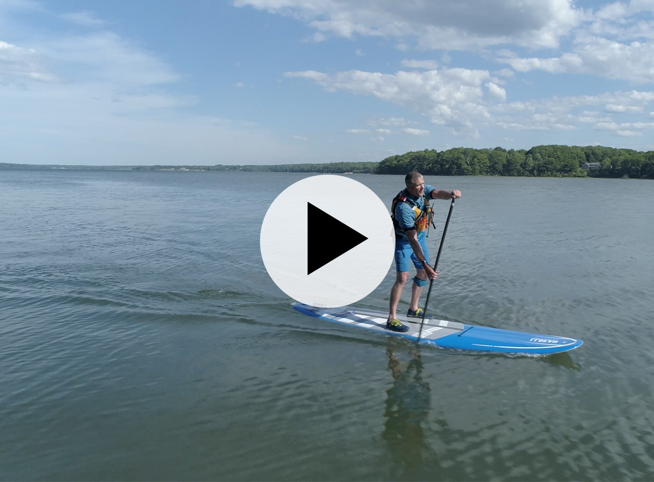 A man paddling a SUP on the ocean, a play video icon in the center.
