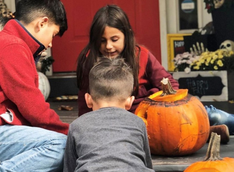 3 kids playing among jack-o-lanterns on a front porch.