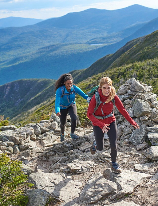 Two women hiking on a rocky path