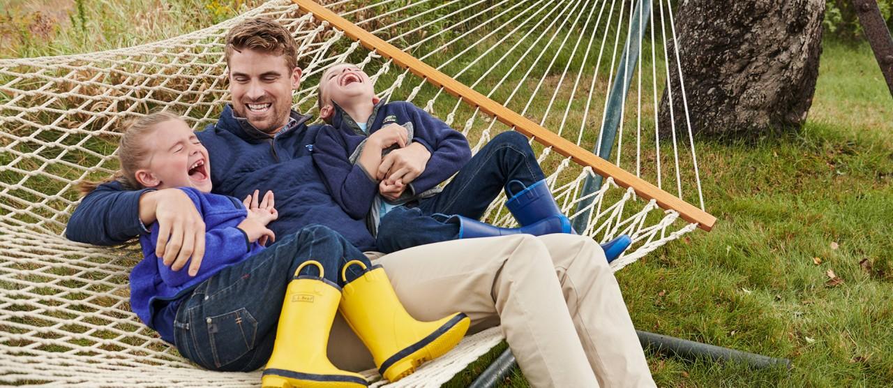 A family swinging in a hammock in their backyard.