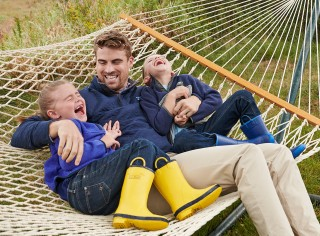 Family swinging on hammock in their backyard.