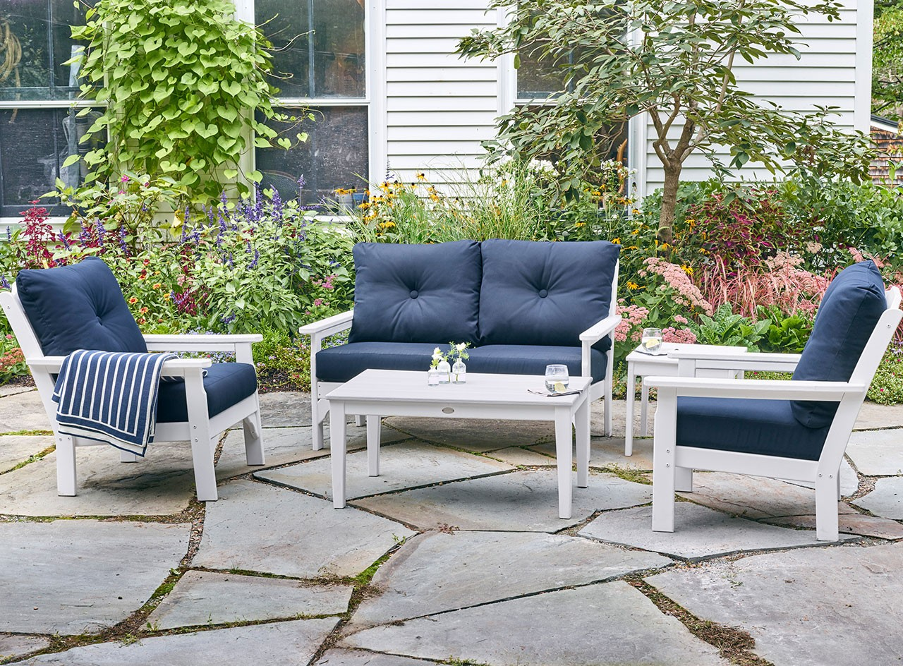 Lush green outdoor patio with 2 L.L. Bean All Weather chairs, a setee and table.