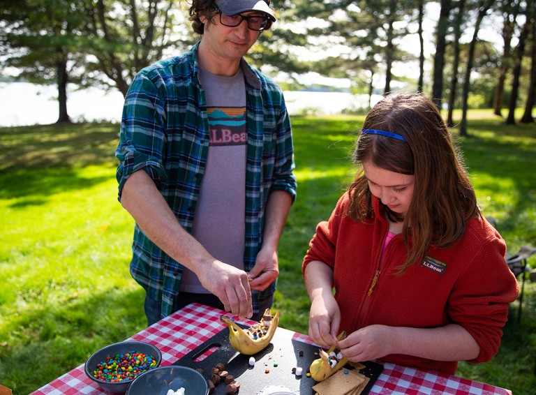 Father and daughter outside preparing a campfire treat.