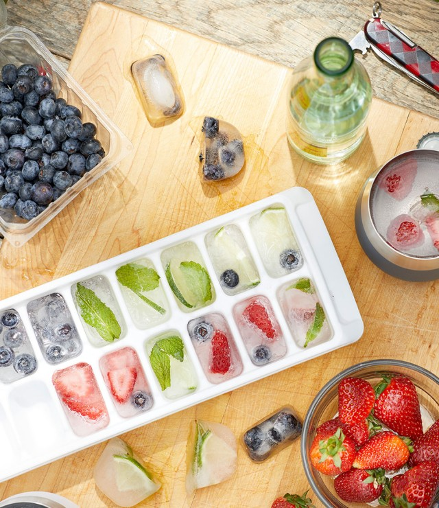 Ice cubes containing blueberries, mint leaves, strawberries or lime slices in an ice cube tray on a kitchen counter.
