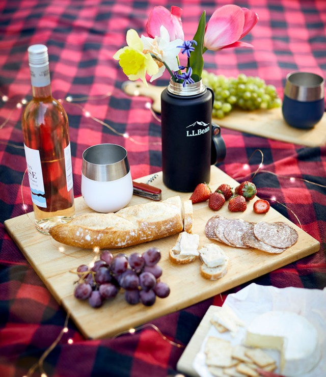 Beautiful outdoor picnic spread on blanket, including a cutting board with baguette, cheese, grapes and wine.