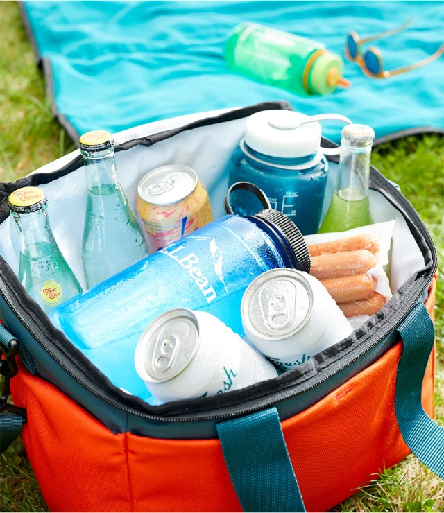 A soft-sided cooler on the grass filled with drinks, hot dogs and half-frozen water bottles.