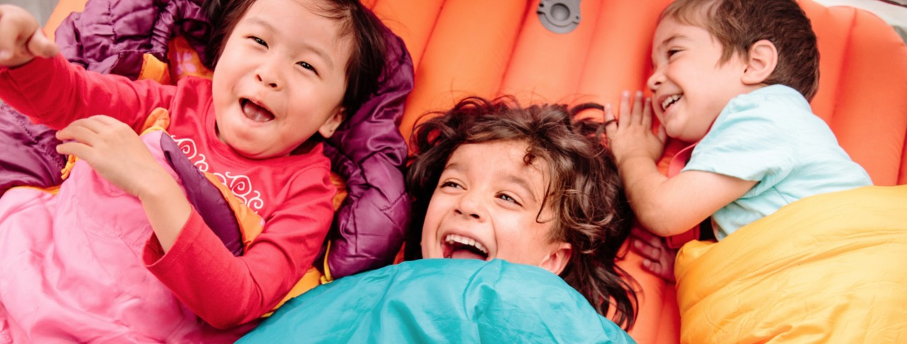 3 laughing kids in sleeping bags
