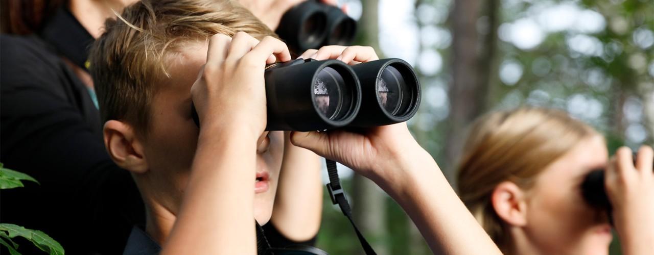 Close-up of family looking through binoculars.