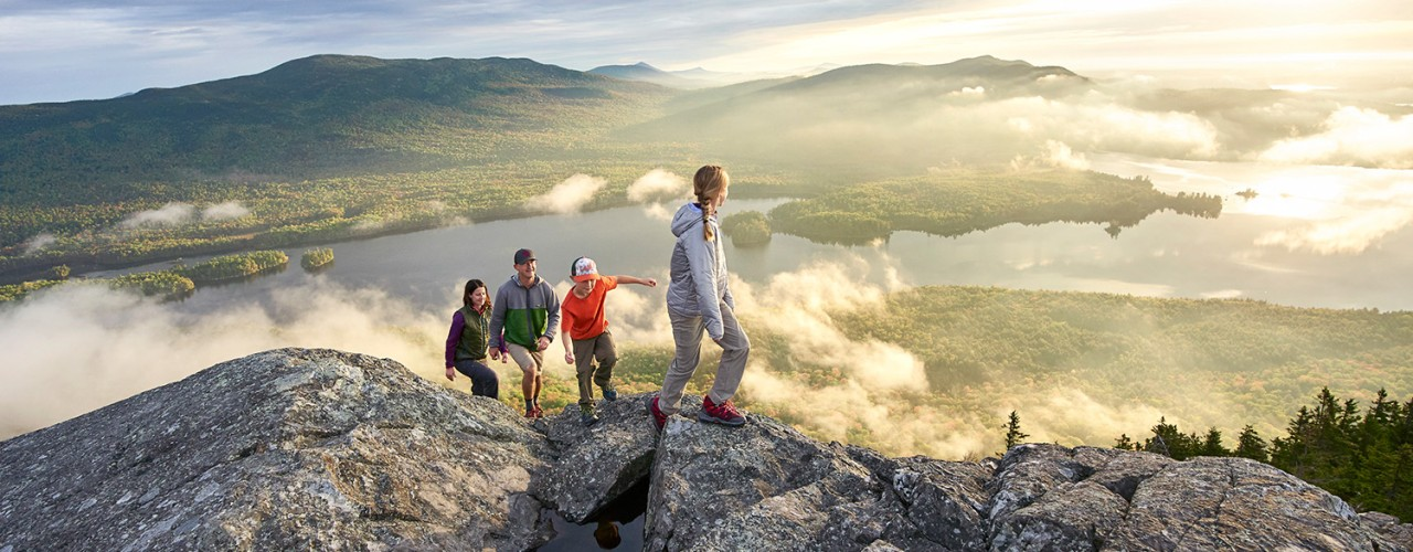 Family of 4 enjoying a beautiful sunrise view on a mountaintop.