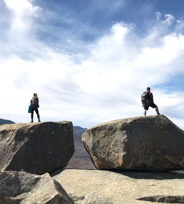 2 hikers atop separate boulders enjoying the view.