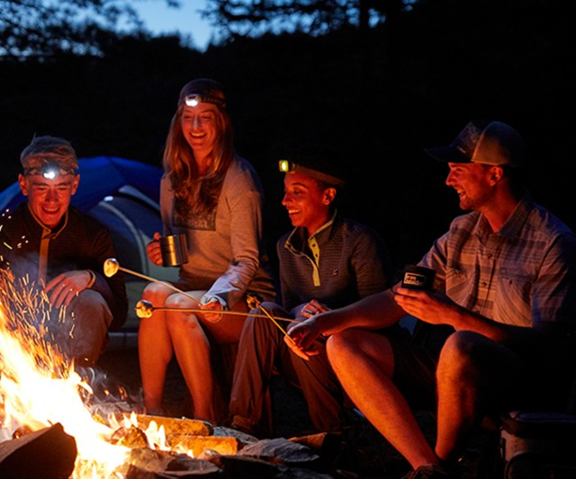 Friends wearing headlamps toasting marshmallows around a fire.