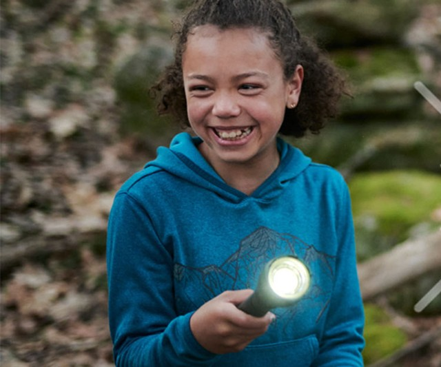 Smiling girl with a flashlight outside at dusk.