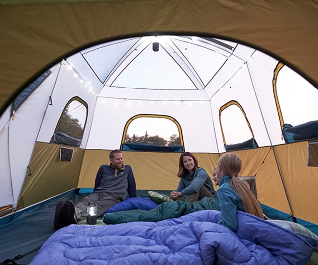 Happy family of 4 sitting and talking in a tent.