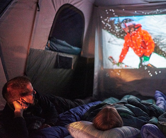 A family lying in sleeping bags in a tent, watching a movie projected on the tent wall.