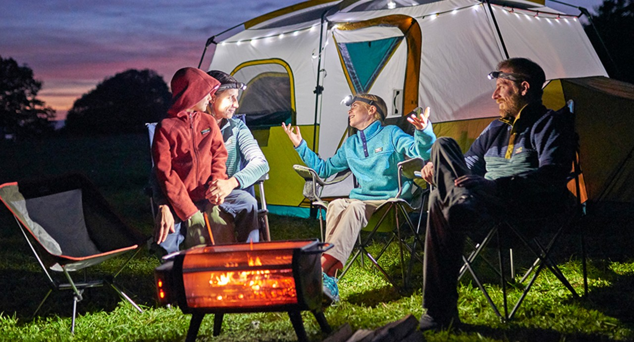 Happy family waring headlamps, sitting and talking around a fire pit, their
