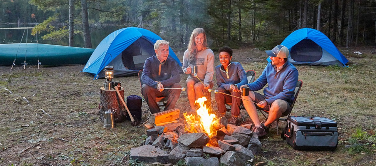 A family sitting around a campfire, tents in the background.