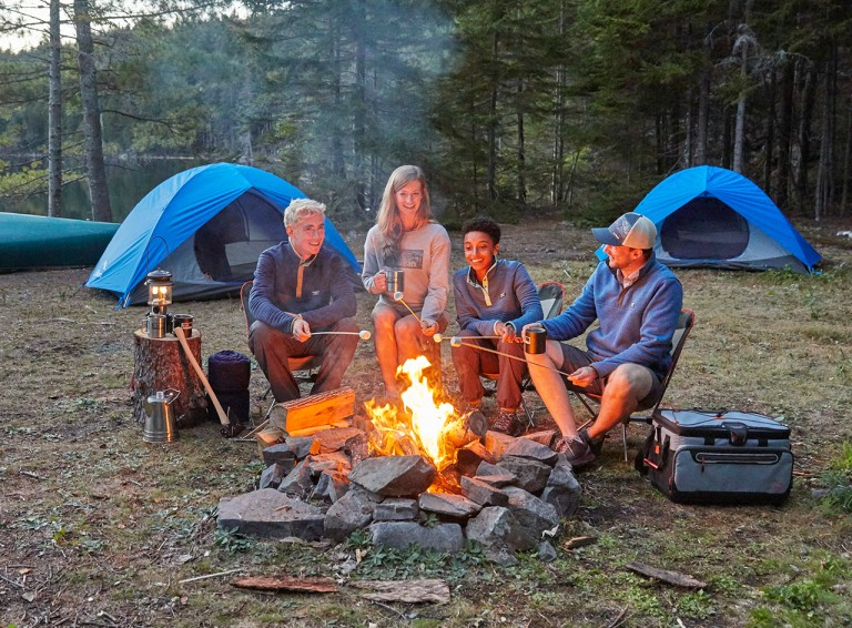 Family sitting around campfire, tents in the background.