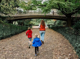 Mom and kids walking down leaf covered walkway.