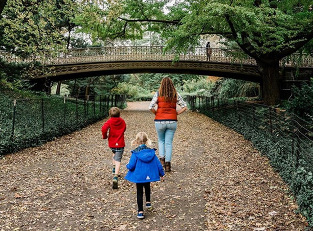 A mom and 2 kids walking along a leaf strewn path.