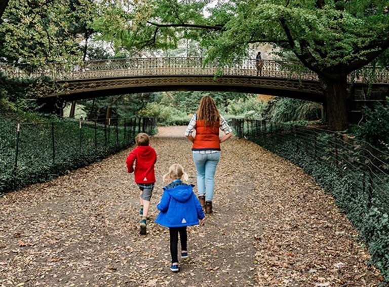A mom and 2 kids walking on a leaf covered path.