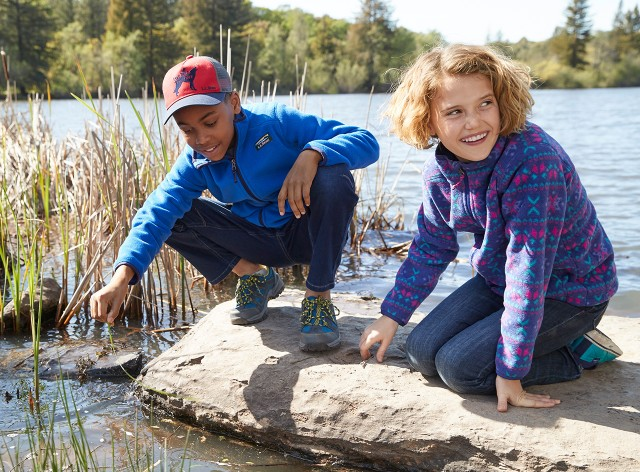 A boy and girl looking in the water on a rock by a lake.