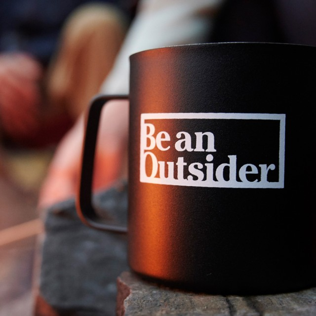 Mug with Be An Outsider logo.