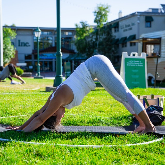 Woman practicing yoga outdoors on a green lawn.