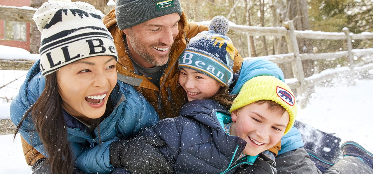 Family of 4 playing in the snow.