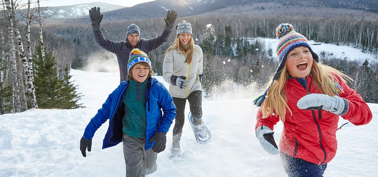 Family of 4 running through the snow on snowshoes.
