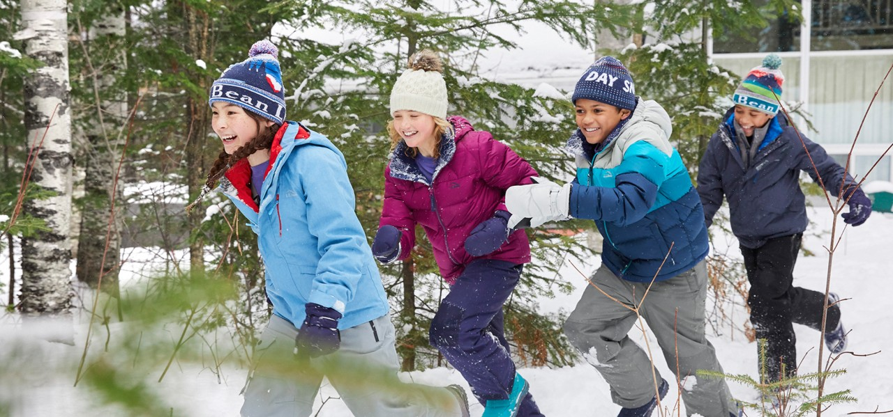 4 happy kids running in the snow.
