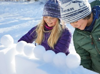 Two children building a snow fort.