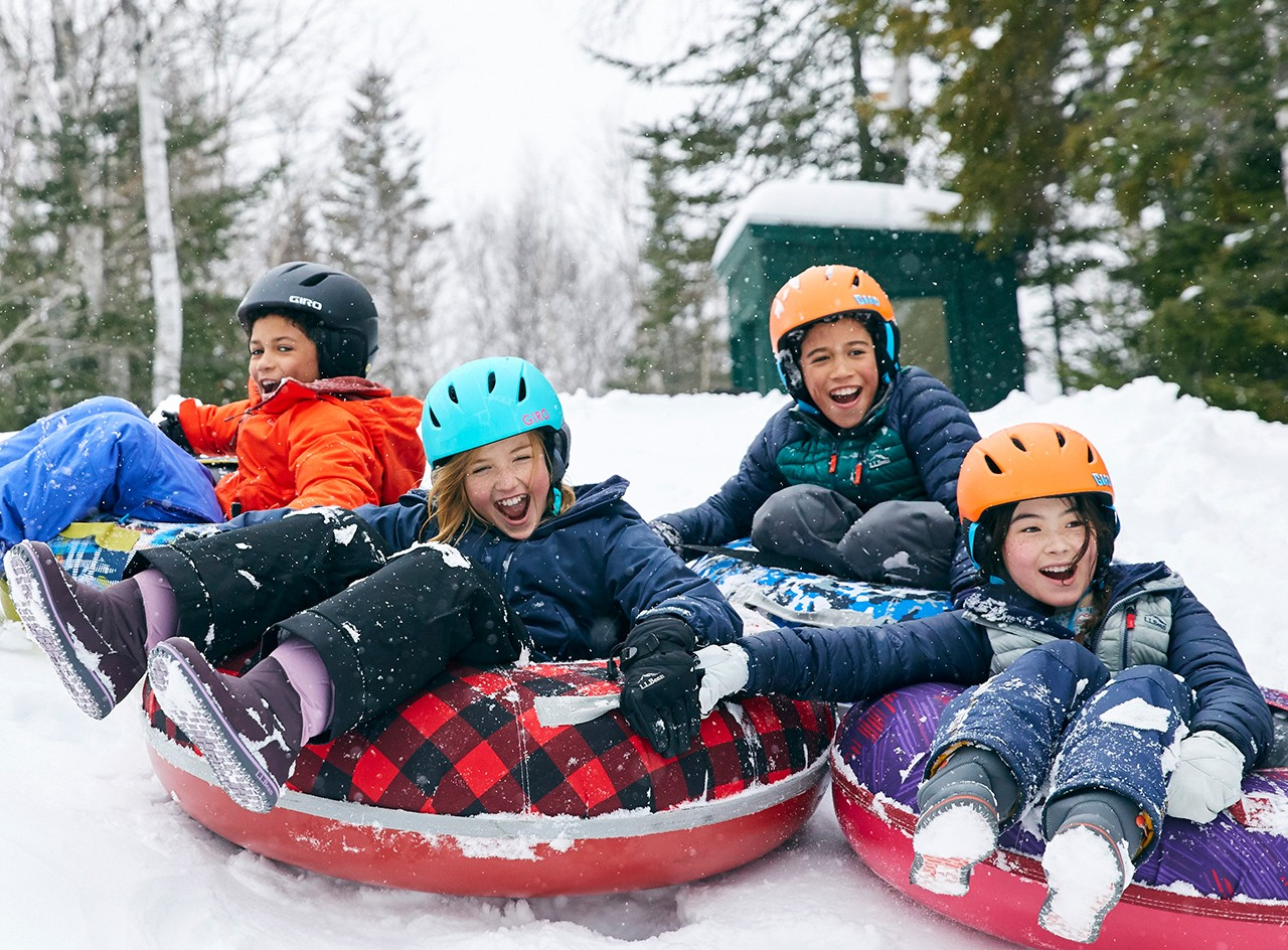 Happy children with helmets sledding in Sonic Snow Tubes.