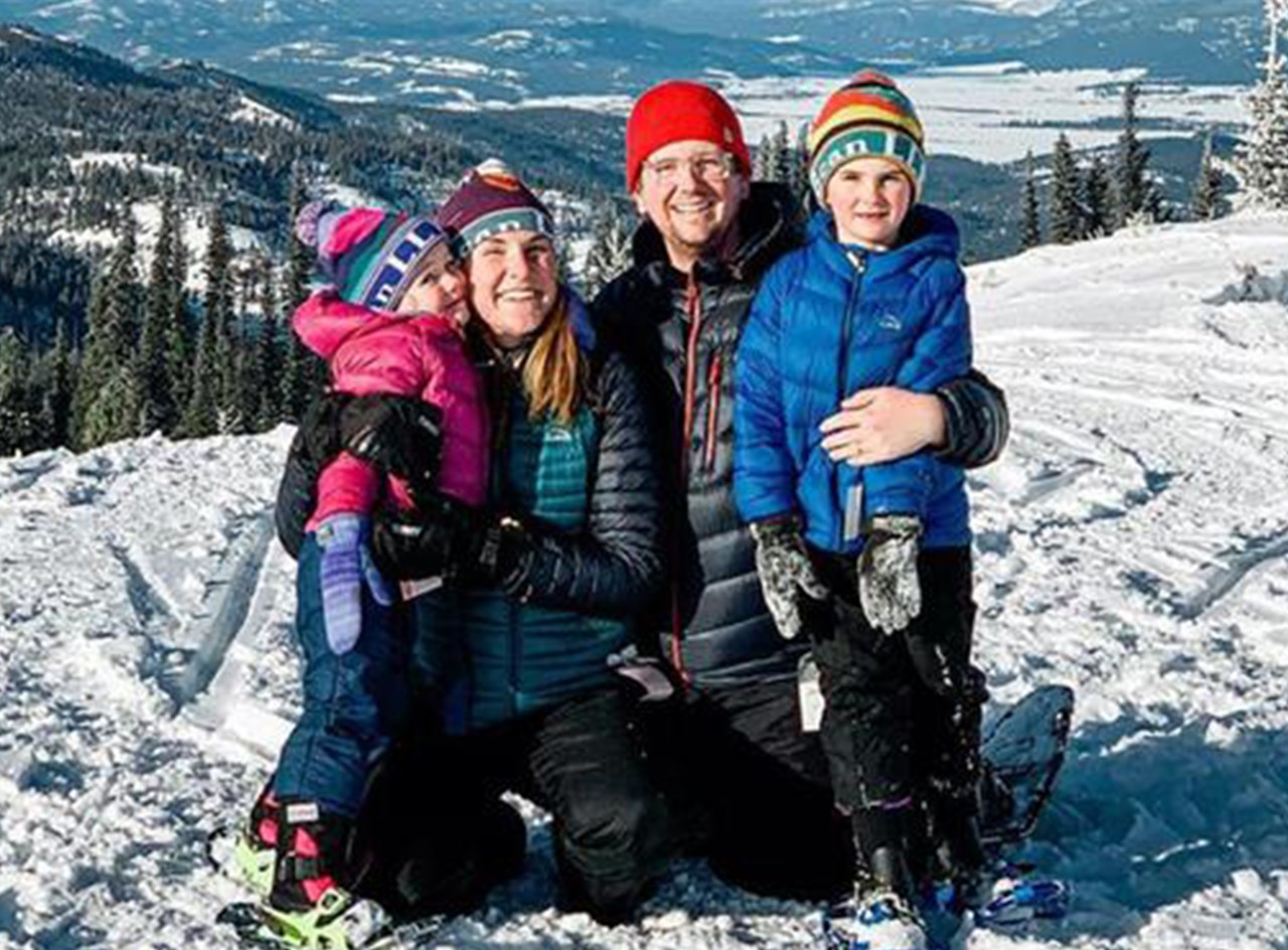The Bowman family, smiling outside on snowshoes in a beautiful mountain setting.