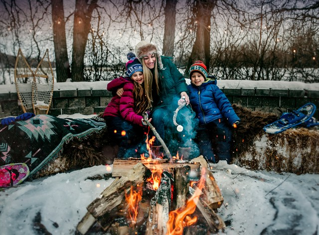 An outdoor fire on a snowy afternoon, a mom and 2 kids sitting on hay bales with blankets roasting marshmallows.