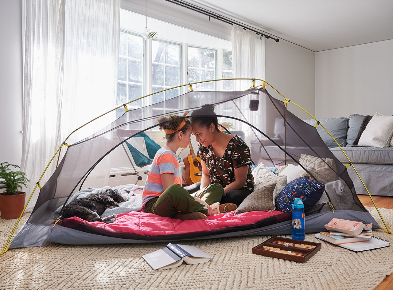 Mom and child camping in a tent in their living room.