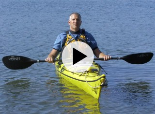 A man holding a kayak paddle sitting in a kayak on the water, a play video icon in the center.