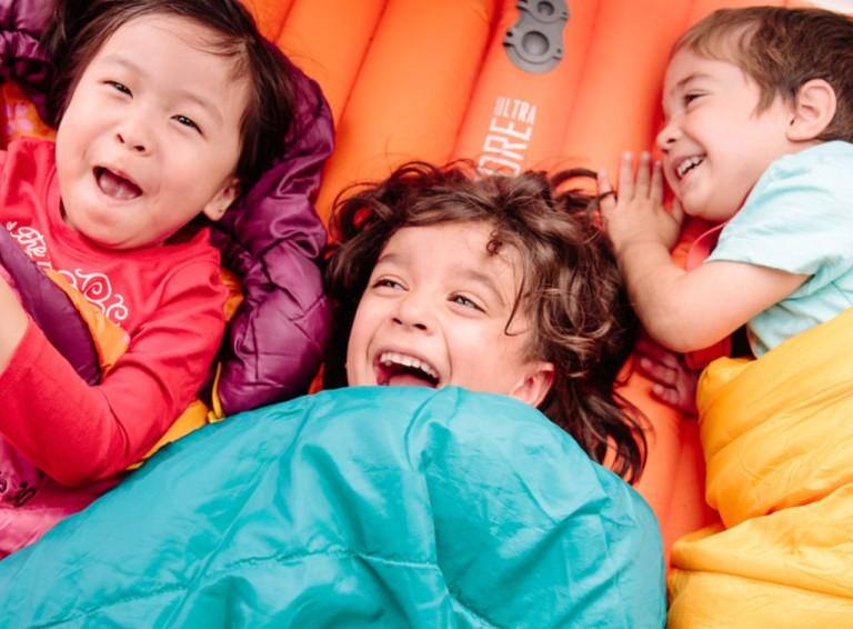 3 laughing kids laying in sleeping bags.