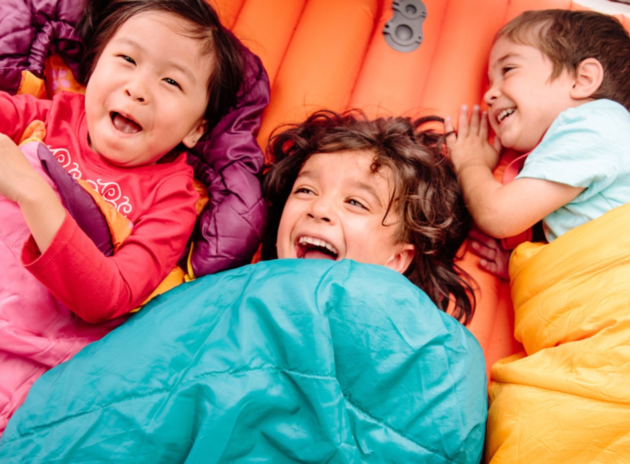 Laughing children cuddled inside sleeping bags in a tent.