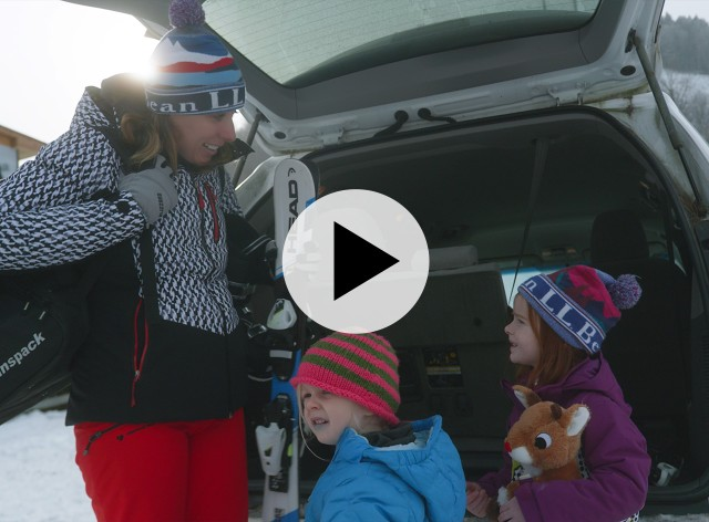 A mom and 2 kids gathering their ski gear from the back of a car.