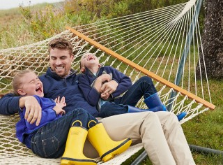 Smiling dad and children laying in L.L.Bean hammock.