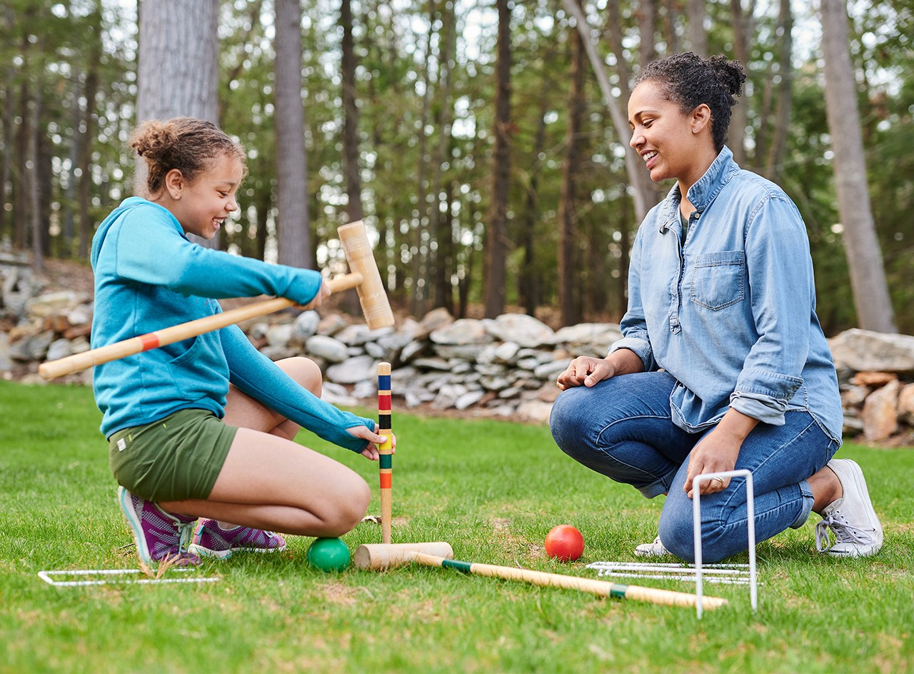 Mom an daughter kneeling down in green grass, setting up an L.L.Bean croquet set.